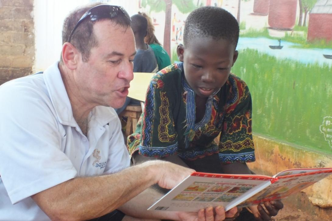 A man reads to a child as part of our volunteering opportunities for seniors in Africa.